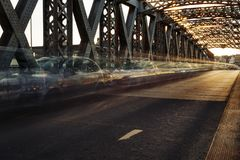 Asphalt road under the steel construction of a city bridge on a sunny day. Urban scene in the bridge tunnel. Long Stock Photography