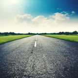 Asphalt road under wide blue skies Stock Photo