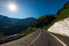 Asphalt road uphill through mountain range. Snow and grass on hillside under the clear blue sky with sun stock photography