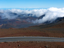 Asphalt Road in volcano country. Road leading up to Haleakala volcano crater. Complete lack of vegetation makes the landscape look extraterrestrial. Blue sky and Royalty Free Stock Images