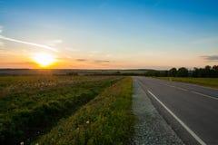 Asphalt Road Way On Sunset von Sun über der Landwirtschaft Lizenzfreie Stockfotos