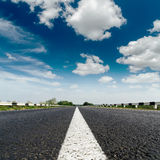 Asphalt road with white line and low dramatic sky. Asphalt road closeup with white line on center and low dramatic clouds in blue sky Stock Photo