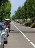 Asphalt road with white line in the middle and the parked cars Stock Photo