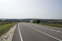 Asphalt road with white markings going through hilly countryside. Asphalt road with white markings going through hilly countryside Royalty Free Stock Photo