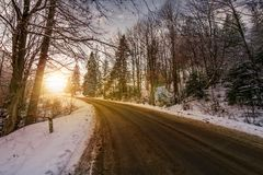 Asphalt road through winter forest at sunset. Beautiful transportation scenery Royalty Free Stock Photo