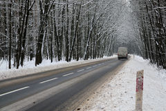 Asphalt road in winter. The photo shows an asphalt road leading through the forest. It`s winter. The surface of the earth and the trees cover layer of snow Stock Photography