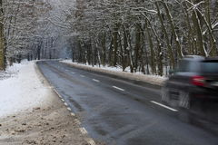 Asphalt road in winter. The photo shows an asphalt road leading through the forest. It`s winter. The surface of the earth and the trees cover layer of snow Stock Photo