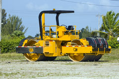 Asphalt roller. An Asphalt/dirt roller sits off to the side waiting the road crews to come through Stock Photos