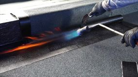 Asphalt roof coating with fire, bitumen water protection stock footage