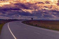Asphalt rural road at sunset. In rural scene use land transport and traveling background Royalty Free Stock Images