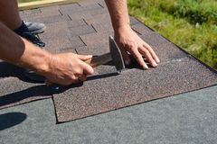 Asphalt shingles installation. Roofer contractor hands installing asphalt shingles on house roofing construction with hammer and. Nails stock photos