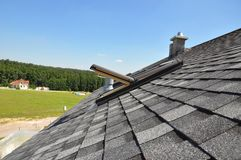 Asphalt shingles roof with open attic skylight window and unfinished roof chimney. Close up royalty free stock photo