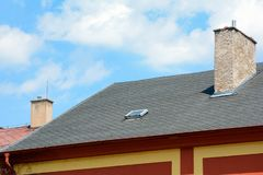 Asphalt shingles roof with skylights windows and rain gutter on the background of blue sky. House with old chimney. Asphalt shingles roof with skylights windows stock images