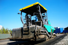 Asphalt spreader on new road to city. Stock Images