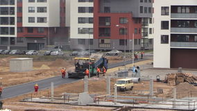 Asphalt spreader and roller machines. Road pavers people stock video footage