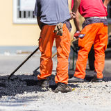 Asphalt surfacing manual labor. Royalty Free Stock Image