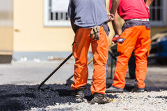 Asphalt surfacing manual labor. Stock Photography