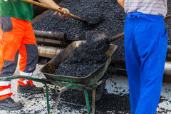 Asphalt surfacing manual labor. Stock Photos