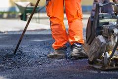 Asphalt surfacing manual labor. Royalty Free Stock Photo