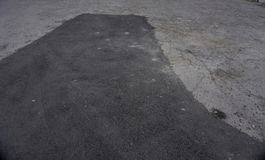 Asphalt tarmac patch on concrete ground repair pavement road in parking lot.  royalty free stock image
