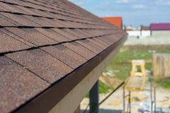 Asphalt tile roof on new home under construction. Selective focus and close up photo of asphalt shingles or tiles installed on top of the roof new residential stock photography