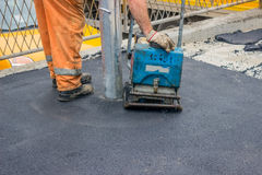Asphalt worker with compactor plate 2 Royalty Free Stock Photography