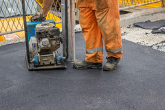 Asphalt worker with compactor plate 3 Royalty Free Stock Image