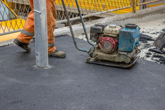 Asphalt worker with compactor plate 4 Royalty Free Stock Image