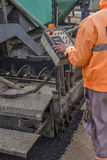 Asphalt worker hand controling paver machine. During road repairing works Royalty Free Stock Image