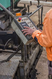 Asphalt worker hands controling paver machine. During road repairing works Royalty Free Stock Images