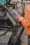 Asphalt worker hands controling paver machine Royalty Free Stock Images