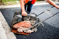 Asphalt worker at road construction site with comp Stock Photo