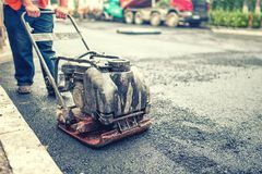 Asphalt worker at road repairing and building site Stock Image