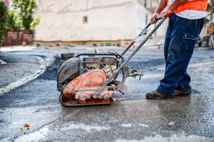 Asphalt worker at road repairing with manual compactor plate Royalty Free Stock Photos