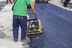 Asphalt worker and vibrating compactor plate Royalty Free Stock Image