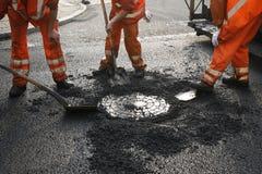 Asphalt workers. Team of Danish asphalt workers lifting a manhole Royalty Free Stock Images