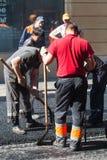 Asphaltage en cours, travailleurs avec des pelles Image stock