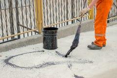 Asphaltarbeitskraft wenden Klebefilm (Bitumen-Emulsion) mit einem Besen an. Lizenzfreies Stockfoto