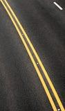 Asphaltbelag mit doppeltem gelbem Frequenzteiler Lizenzfreies Stockfoto