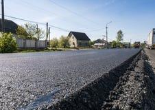 Asphalte noir fraîchement étendu de bitume avec un bord élevé au gravier montrant la structure Pose d'un nouvel asphalte sur images stock
