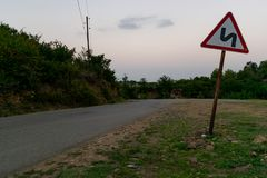 Asphalted mountain road with sharp sharp turn near the cliff. Traffic sign. stock photography