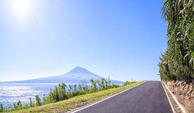 Asphalted road in Azores runs along the grassy shores of the Atlantic Ocean, on a background of of an extinct volcano Royalty Free Stock Image