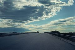 An asphalted road with a car against the sky with clouds. stock photos