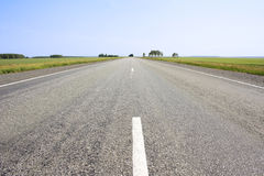 Asphalted road with a dividing strip Royalty Free Stock Photos