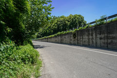 Asphalted road at head of fenced highway bridge in sunny summer Royalty Free Stock Images