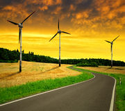 Asphalted road with wind turbines Stock Photography