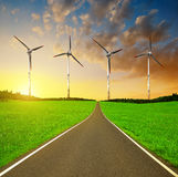 Asphalted road and wind turbines Royalty Free Stock Photos
