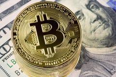 Asphaltieren Sie bitcoin Münzen auf hundert Dollarscheinhintergrund Stockfotografie