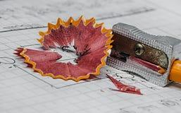 Asphaltieren Sie Bleistiftspitzer und Schnitzel auf einem Notizbuch Stockbilder
