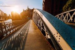 Asphaltieren Sie Bogenbrücke mit Nieten im Speicherstadt von Hamburg während der goldenen Stunde des Sonnenuntergangs mit Sonnend lizenzfreie stockbilder